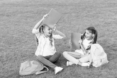 Schoolgirls little children school yard with books, learning language concept