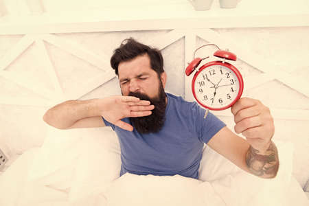 Need to Sleep longer. man hipster want to sleep. Male On Bed yawning. mute the alarm clock.