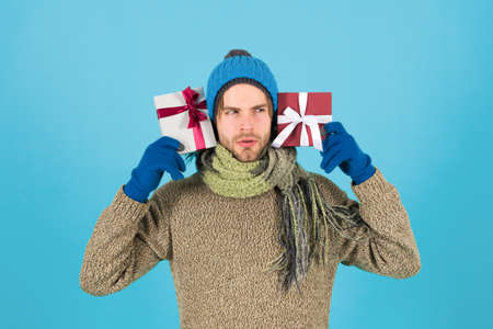 What is inside. Man bearded handsome wear winter hat scarf gloves hold two gift boxes. Zdjęcie Seryjne