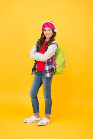 Happy child listen to audio course in modern headphones carrying school bag in casual fashion style, listening