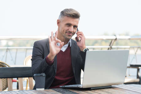 Now thats what I call OK. Handsome man show OK talking on phone. Agreement and permission. Project manager work in cyber cafe. Modern lifestyle. Business communication. Mobile technology