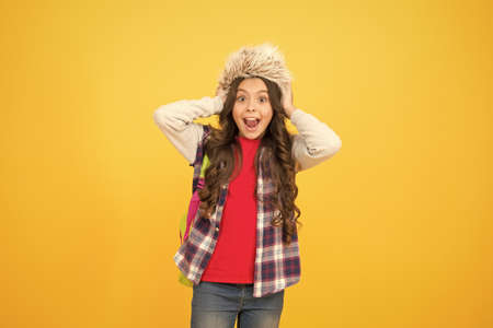 what a great surprise. carefree child pupil. small girl wear earflap hat. winter school time and holidays. winter courses education. schoolgirl backpack yellow background. course selection period