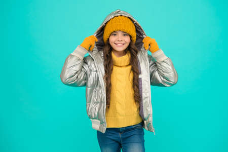 happy child feel comfortable and warm in padded jacket and knitted clothing in winter weather, cold winter