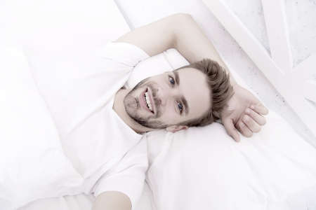 Handsome man relaxing in bed. Establish regular nightly sleep pattern. Practice calming activities such as meditation before going to bed. Healthy sleep concept. Tips promoting healthful sleep habits