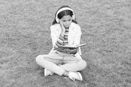 Achieving High Standards. small girl reading book. literature for kids. write childhood memories. smart kid in headset. back to school. kid study online in park. listen music on green grass with book Imagens