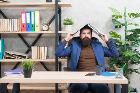 Serious businessman in formal style hold laptop on head . Stock Photo