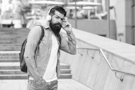 Engineered for modern life. Bearded man wear headphones outdoors. Listening to music in modern age. Hi-Fi audio. Digital sound. Modern technology. Modern lifestyle