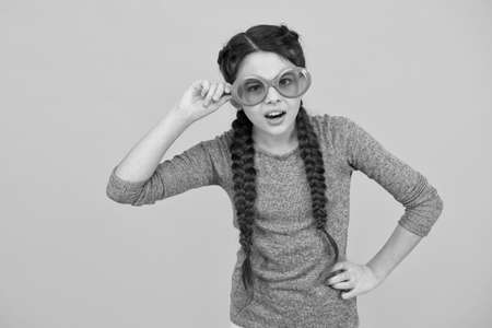 change your body language. small girl has funny look. kid hairstyle fashion. amazed child with hairdo. teen has party fun. Hair braided in braids. little beauty wear party glasses. happy childhood Standard-Bild