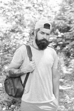 Relaxing hiking Experience. Bearded man carry backpack. ready for camping. male tourist wear cap. sport and fitness clothes. Confident and handsome brutal man. brutal caucasian hipster with moustache Standard-Bild