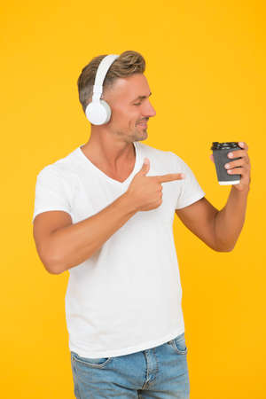 Unshaven man listen to music and point index finger at takeaway coffee cup promoting and advertising yellow background, carry-out service Standard-Bild