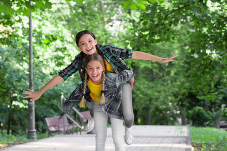 Happy childhood friends have fun piggybacking in park on summer day, holidays