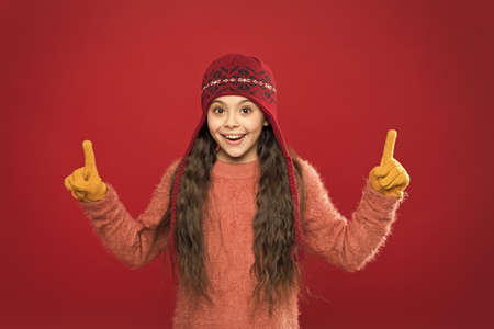 Look here. Little girl winter fashion accessory. Small child wear hat burgundy background. Cute model enjoy winter style. Presentation concept. Winter outfit. Little kid wear knitted hat. Stay warm