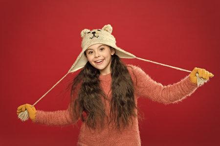 Cute model enjoy winter style. Teddy bear. Being cute bear. Winter outfit. Little kid wear knitted hat. Stay warm. Little girl winter fashion accessory. Small child long hair wear hat red background Standard-Bild