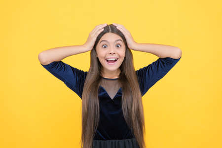 is that for real. shocked teen girl with long hair. express positive human emotions. amazed cute child. kid fashion and beauty. hairdresser concept. teenager on yellow background. happy childhood