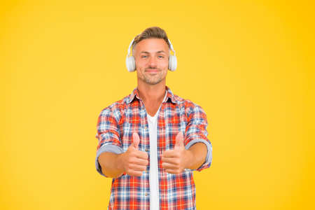 Good music is just a pair of headphones away. Happy man show thumbs ups listening to music yellow background. New technology. Modern life. Fun and entertainment. Loud and clear Stock fotó