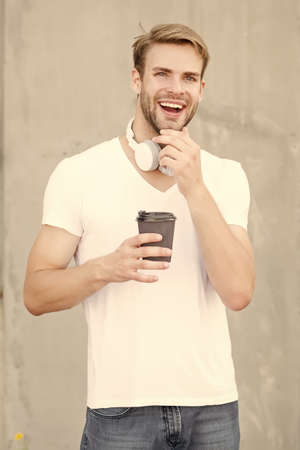 Energy and optimism. Happy guy hold hot cup outdoors. Enjoying takeaway tea or coffee. On-the-go caffeine energy break. Tasty energy drink. Boosting energy in morning. Fashion music accessory Standard-Bild