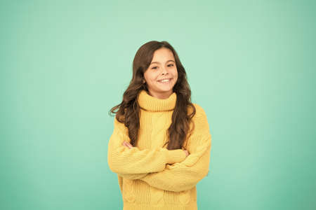 Positive mood. Kids psychology. Adorable smiling girl wear yellow sweater turquoise background. Positivity concept. Good vibes. Emotional baby. Positive child. Positive attitude to life. Inspiration