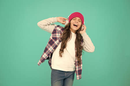singing with mp3 player. small child long hair enjoy stereo. happy childhood. happy girl turquoise background. smiling teenager listen music in headphones. little kid casual style. autumn mood tune Standard-Bild