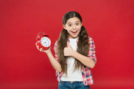 happy child girl with mechanical alarm clock showing thumb up, holiday time