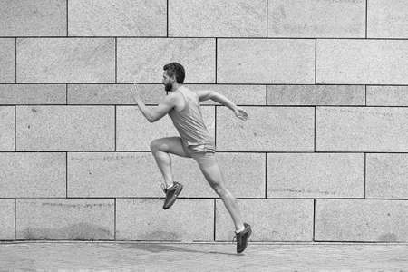 male runner. man running to success. sport success. Striving for victory. active man in sport clothing jumping while exercising outdoors. guy sprinting on the street. Leap forward Zdjęcie Seryjne