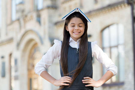 Happy funny kid in school uniform hold study book on head keeping eyes closed outdoors, imagination