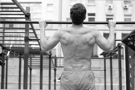 back view of man doing pull up at the gym. concept of sport. exercises in fitness gym. Male shirtless model doing exercises outdoors. The fit athlete doing exercises at stadium. be healthy