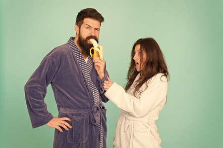Food for health. Healthy breakfast. Couple sleepy faces domestic clothes eat banana. Couple in love bathrobes. Advice relationships surviving quarantine. Morning routine. Sharing food. Healthy food Zdjęcie Seryjne
