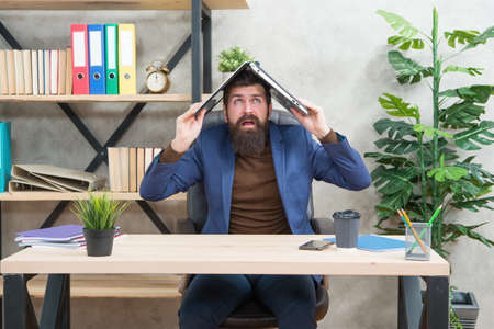 Crazy trader in formalwear hold notebook computer on head sitting at desk in business office, e-commerce