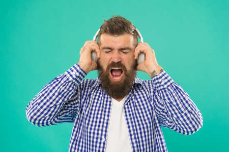 mature male hipster enjoy music in headset on blue background, modern device