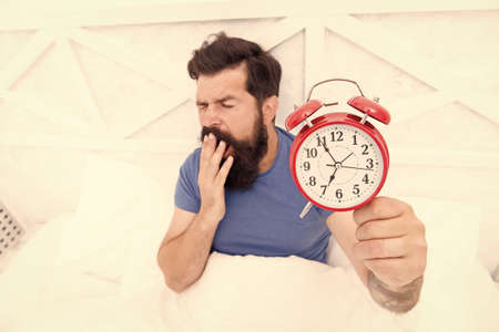 Time to wake up. Healthy habits. Beginning of awesome day. Wake up early every morning. Health benefits of rising early. Waking up early gives more time. Hipster bearded man in bed with alarm clock