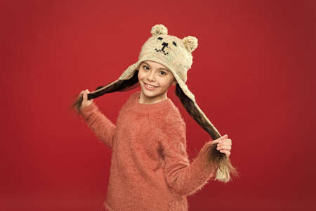 Happiness and joy. Little kid wear knitted hat. Little girl winter fashion accessory. Winter outfit. Small child long hair wear hat red background. Cute model enjoy winter style. Adorable small bear.