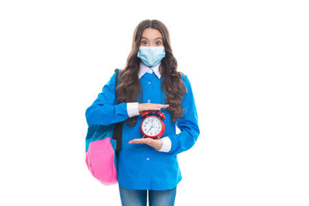 Surprised school child wear protective mask to prevent COVID-19 spread holding alarm clock, deadline