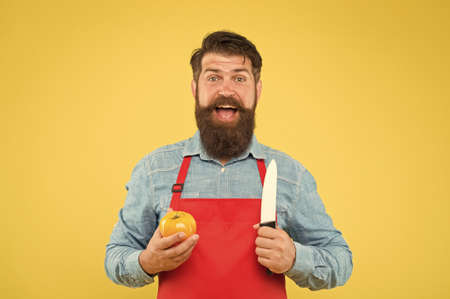 Fresh salad recipe. Mature man hold knife and vegetable. Safe cutting. Cutting veggies. Ultimate list of cutting techniques every chef should know. Chef prepares meal. Bearded man prepare tomato Foto de archivo