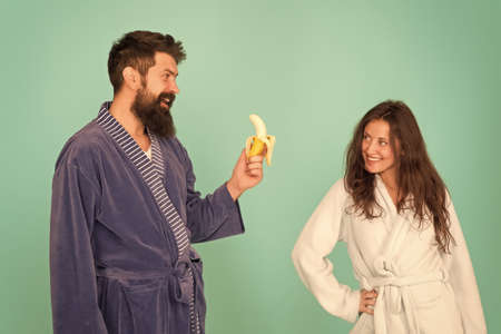 Sharing food. Healthy food. Food for health. Healthy breakfast. Couple sleepy faces domestic clothes eat banana. Couple in love bathrobes. Advice relationships surviving quarantine. Morning routine Zdjęcie Seryjne
