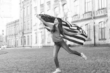 Little girl with american flag outdoors architecture background, inner freedom concept