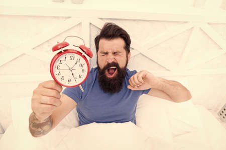 Health benefits of rising early. Waking up early gives more time. Hipster bearded man in bed with alarm clock. Time to wake up. Healthy habits. Beginning of awesome day. Wake up early every morning