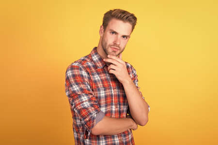 he know better. handsome guy with bristle on face. male beauty standard. fashion model on yellow background. unshaven man. denim clothing trend. barbershop salon. man in casual checkered shirt
