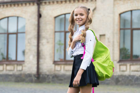 Free schooling. Happy child carry backpack outdoors. Formal schooling. School education. Learning activities. Fashion uniform. Back to school Foto de archivo