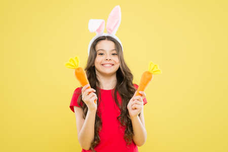 Holy Week activities. Healthy food. Child bunny ears. Diet for health. Benefit of eating carrot. Easter carrot. Girl hold carrot. Play with food. Spring tradition. Playful child yellow background