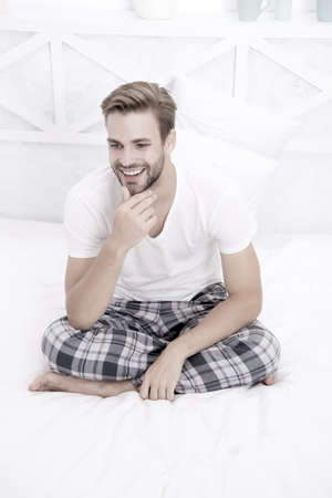 start day smiling. Menswear pajamas for home relax. male full of energy. happy man sit in pajama. man relax in bed. perfect morning. guy touch his unshaven beard. feeling cosy and comfortable