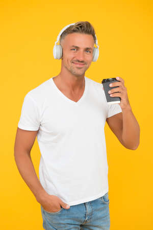 Caucasian middle-aged man drink takeaway coffee listening to music in casual fashion style yellow background, drinking