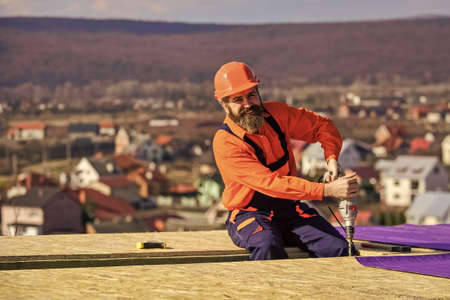 Picky inspector. new roof under construction residential building. builder use drill. professional master repair roof. Flat roof installation. roofing felt. Roofer in special protective work wear