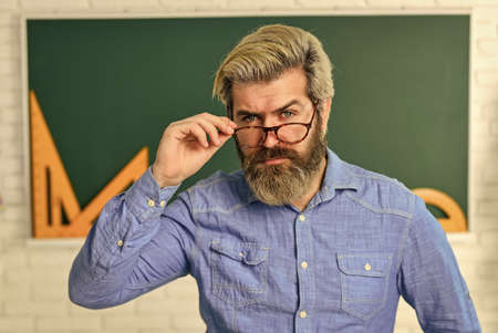 serious bearded teacher in glasses. back to school. develop logic and creativity. start the brain engine. physics research. math teacher at blackboard. education. exact sciences