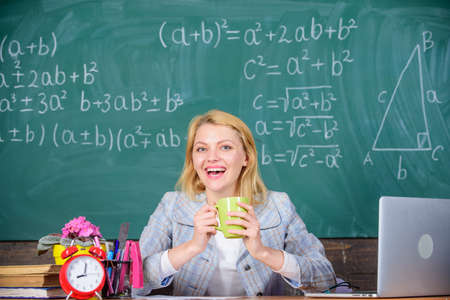 Pleasant relax after classes. Working conditions which prospective teachers must consider. Working conditions for teachers. Woman smiling teacher holds mug drink classroom chalkboard background