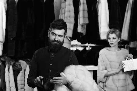 Lady and man with beard on fur coats background. Woman in pink fur coat with man in fashion shop.