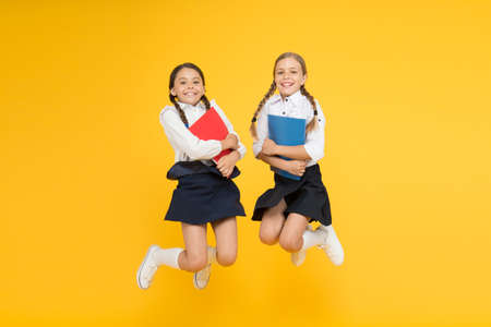 funny education. little girls in school uniform. cheerful classmates with workbook. kids learning grammar. back to school. dictionary notebook. Get information. reading story. childrens literature 版權商用圖片