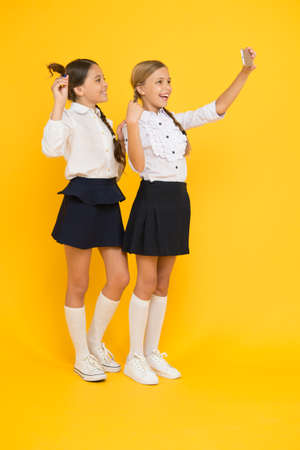 social network. happy friends with smartphone. kids make selfie photo, friendship. small girls in school uniform. back to school. educational blog. digital technology. online education. knowledge day Reklamní fotografie