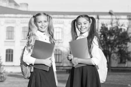 Friendship doubles joys. Happy children back to school. Little kids hold books outdoors. School friends enjoy friendship. International friendship day. Friendship bonds. Childhood friends Archivio Fotografico