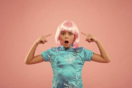 what is going on. Hair salon. Fashion and beauty. surprised girl pointing at wig. Party child in chinese style. small chinese girl in pink wig. kid in traditional Chinese gown. retro chinese girl Stock fotó
