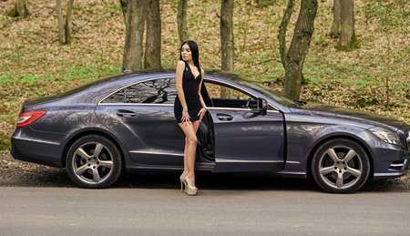 Driver lady. Beauty and fashion. Woman in dress. My car is broken. Defenseless naive girl needs help. Sexy girl elegant dress at road. Sexy girl and luxury car. Escort and services